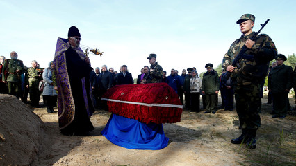 An Orthodox priest takes part in a reburial ceremony for the remains of Russian Imperial Army servicemen who died during the First World War, near the village of Makarovtsy