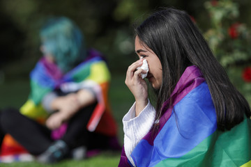 Girl draped in a rainbow flag wipes her tears after taking part in a protest against proposed changes to the constitution in Burcharest