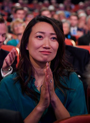 The wife of Britain's Foreign Secretary Jeremy Hunt, Lucia Guo, listens to her husband address the Conservative Party Conference in Birmingham