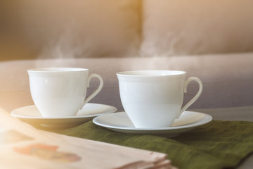 Two white coffee cups with soft smoke stream put on plate and dark green cloth nearly newspaper in the living room and sun lighting from window. Selective focus.