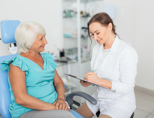 Doctor sitting in office with mature patient talking and holding medical chart