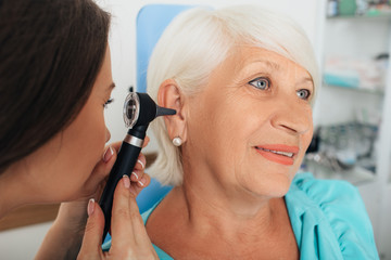 Mature woman getting ear exam at clinic , doctor examining elderly patient ear , using otoscope