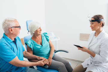 Two senior patient in ENT clinic talking with doctor