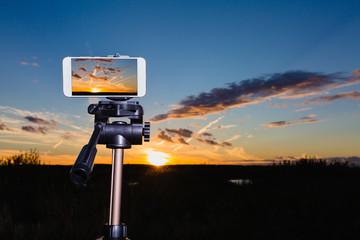 Smartphone on tripod capturing image of stunning sundown