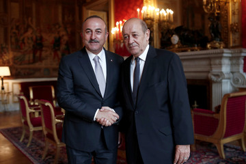 French Minister for Foreign Affairs Jean Yves Le Drian and his Turkish counterpart Mevlut Cavusoglu, pose for the media prior to their bilateral meeting at the Quai d'Orsay in Paris