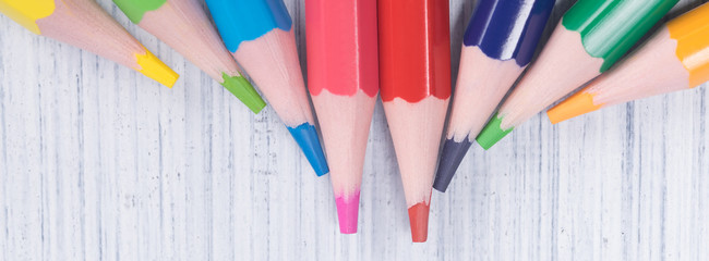 colored pencils in a pile, long background