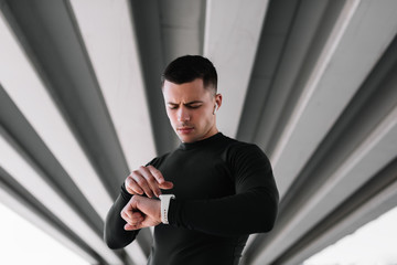 Portrait of muscular athlete listening music wearing wireless headphones and using smartwatch standing on the street . Professional sportsman or runner  in fitted suit ready to workout. Training.