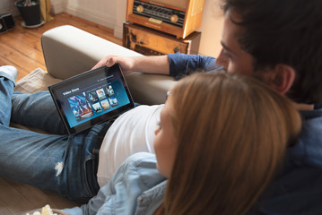 Couple using digital tablet for watching movie on VOD service