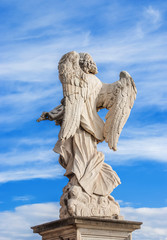 Angel marble statue with beautiful clouds. A 17th centuty baroque masterpiece at the top of Sant'Angelo Bridge in the center of Rome
