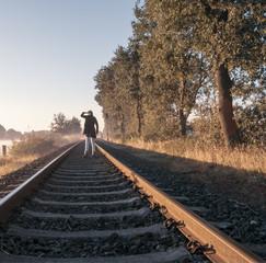 Einzelne Frau steht auf Bahnschiene und schaut in den Sonnenaufgang.
