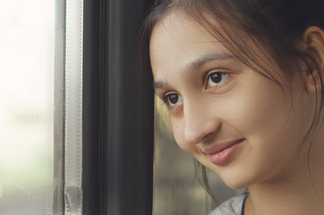 A young beautiful girl looks out the window and smiles. Close-up portrait.
