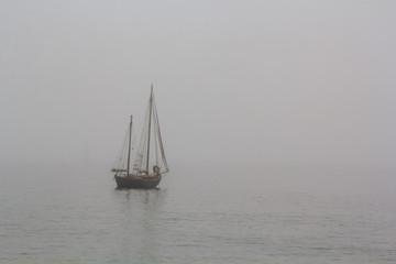 Tall ship sailing in the sea in fog