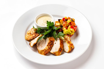 Plate with fried chicken breast served with ratatouille vegetables and sauce isolated at white background.