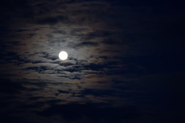 Mysterious night sky with moon and clouds.