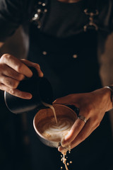 Barista pouring coffee into a cup