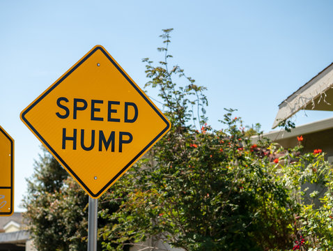Speed hump yellow street sign in a local neighborhood street