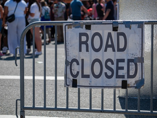 Make shift road closed sign hanging on barrier with crowd in back