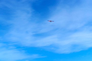 a small aircraft soars in the blue sky, glider in the sky