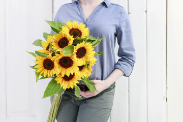 Wall Mural - Woman holding bouquet of sunflowers.