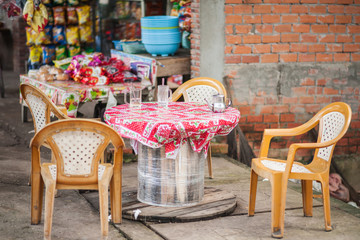 Simple outdoor cafe and seating area where tourists can enjoy Vietnamese coffee and other beverages at a local market. Mekong River Delta, Vietnam.