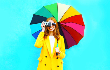Happy smiling woman takes a picture on retro film camera holds colorful umbrella in yellow coat jacket on blue background