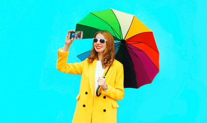 Happy smiling woman with colorful umbrella taking selfie by smartphone on blue background