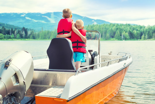 Two brothers swim on a motor boat on the lake.