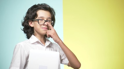 Portraits of a teenager in school uniform and glasses on a colored background. Funny guy. concept of learning. A teenager is holding a laptop, looking at the camera, smiling and making funny faces