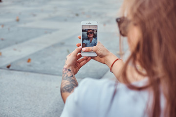 Close-up photo of young girl in sunglasses makes a selfie outdoors.