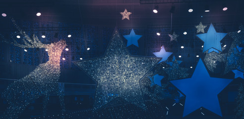 Christmas winter new year holidays Dark night background with Christmas stars lights spotlights with blue pink lilac lights
