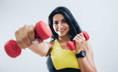 Handsome muscular woman working out with dumbbells.
