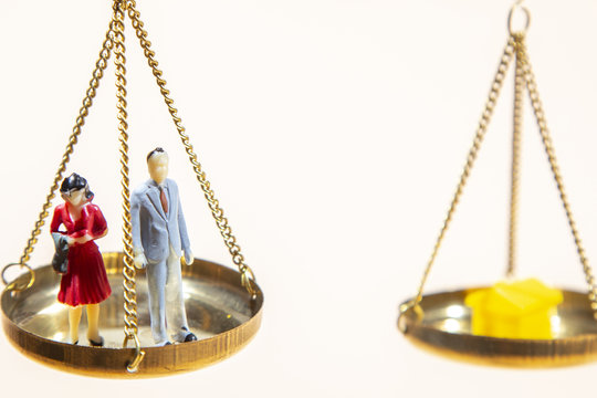 Balance between man and woman on gold scale and real estate