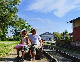 Adorable little girl and boy on a railway station, waiting for the train with vintage suitcases. Traveling, holiday and chilhood concept. Travel insurance concept. Vacation trip