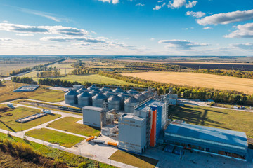 Large modern silos granary steel tanks or containers for silos, wheat and other cereals. Industrial agriculture, aerial view