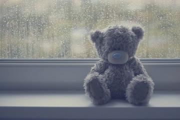 Gray teddy bear on a window sill in rainy weather