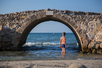 Young boy in swimsuit stands under an old stone bridge in water of sea, in Greece