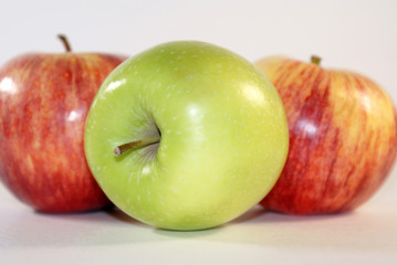 Green and red apples on a white background.