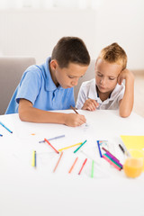Little boys having fun and coloring at home