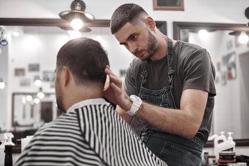 Barber makes a haircut to the client. Men's haircut in barbershop.