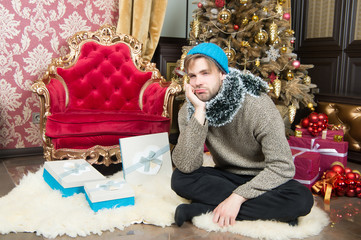 Guy with unhappy face sit at Christmas tree