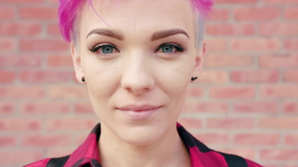 A happy smiling woman with a pink short hair against a brick wall background. Medium shot. Soft focus