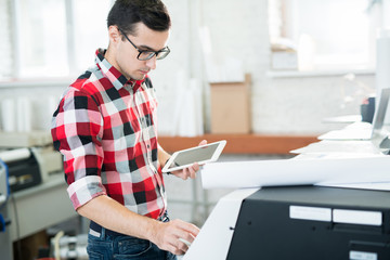 Papier Peint - Serious busy handsome male technician in glasses wearing checkered shirt using tablet to operate large format printer in workshop