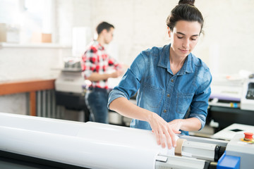 Papier Peint - Serious confident young woman  with hair bun loading wide format printer while working at printing house