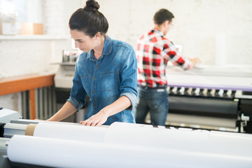Serious concentrated woman in denim shirt standing at large format printer and choosing program while working in printing office