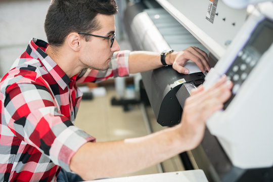 Serious thoughtful handsome young engineer in shirt examining wide format printer while holding inspection in printing house