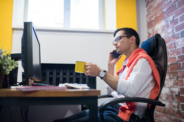 Serious pensive young male manager in glasses sitting at desk and drinking coffee while talking by phone in loft office