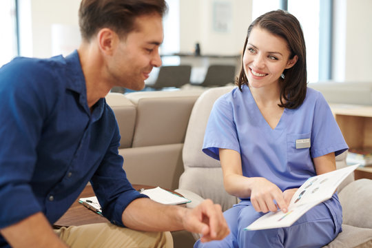 Portrait of smiling young nurse offering brochure to patient in hall of modern clinic, copy space