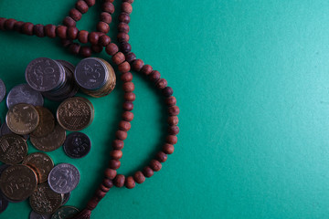 Islamic Banking/Financing Conceptual with rosary and coins on a green background.