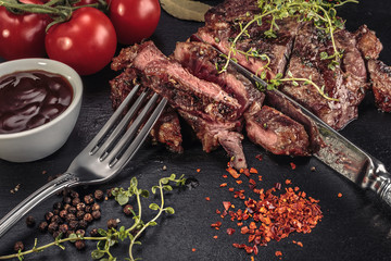 Grilled sliced beef steak at slate board with herbs