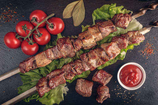 Shish kebab with tomatoes at the slate black board